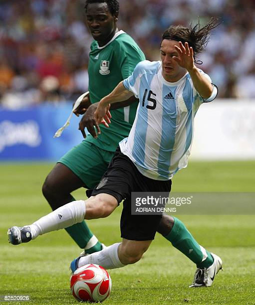 Nigerian defender Dele Adeleye challenges Argentinian forward Lionel Messi during the men's Olympic football final Argentina vs Nigeria at the...