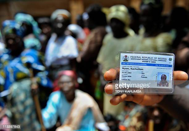A Nigerian displays the card of an elederly voter aged 107 at a polling station on April 16 2011 at Jos' Du area in Nigeria's Central Belt during the...