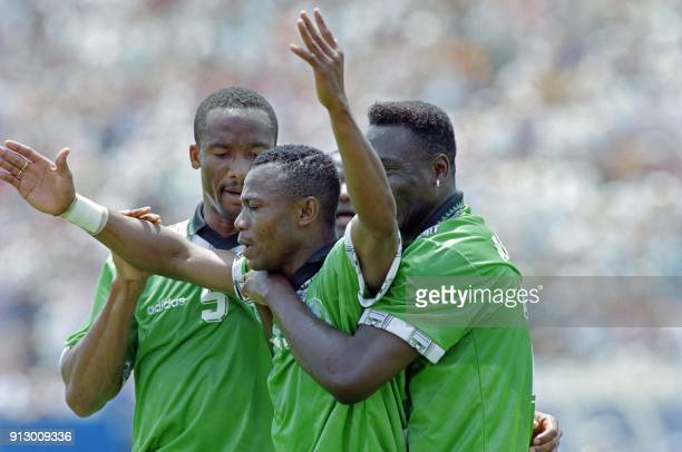 Nigerian Emmanuel Amunike celebrates with teammates Okechukwu Uche and Daniel Amokachi after scoring his goal against Italy during the first period...