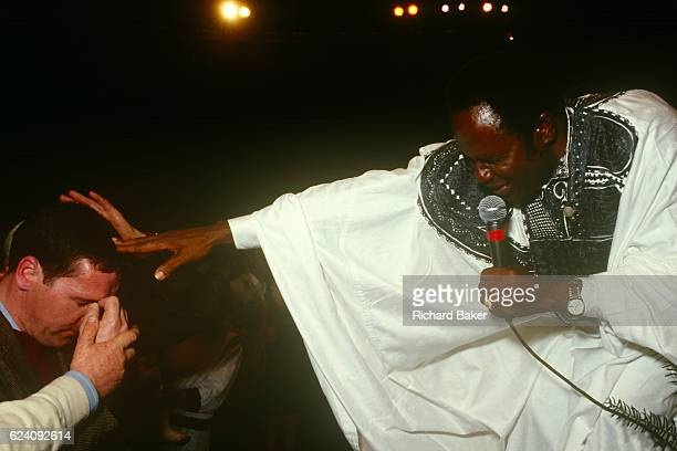 Nigerian evangelist, Rev. Benson Idahosa places his hand on the head of a Born-again Christian during a Christian rally at Butlins Bible Week during...