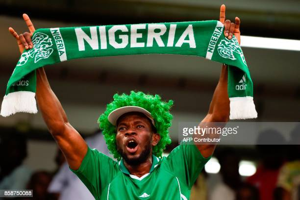 A Nigerian fan waves a scarf as he celebrates after the FIFA World Cup 2018 qualifying football match between Nigeria and Zambia in Uyo Akwa Ibom...