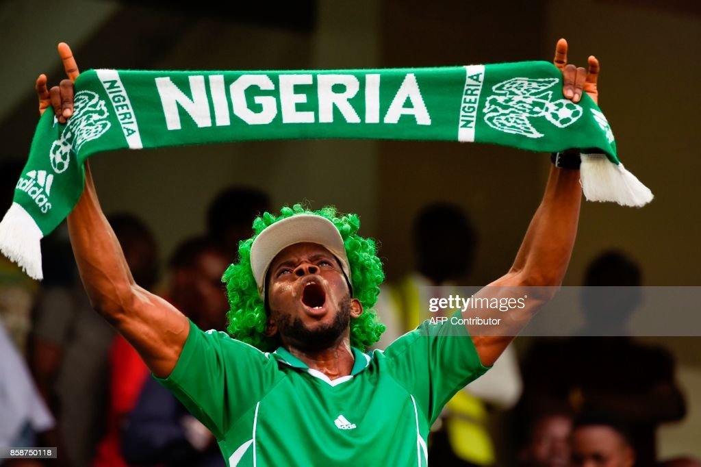 A Nigerian fan waves a scarf as he celebrates after the FIFA World Cup 2018 qualifying football match between Nigeria and Zambia in Uyo, Akwa Ibom State, on October 7, 2017. /