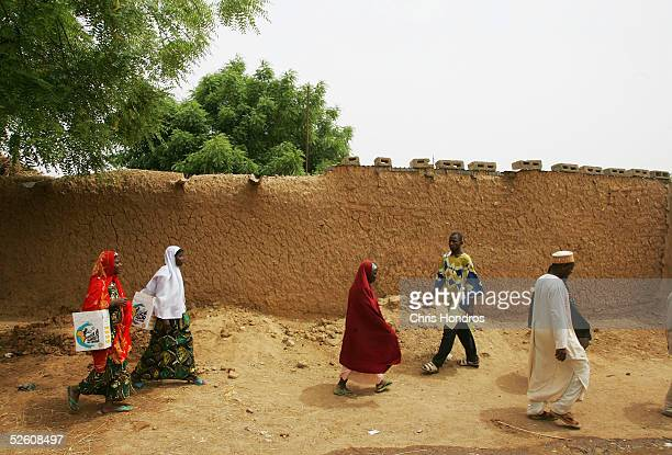 Nigerian field workers for the World Health Organization make their way with polio vaccine down a dusty lane in a remote area April 9, 2005 in Rimin...