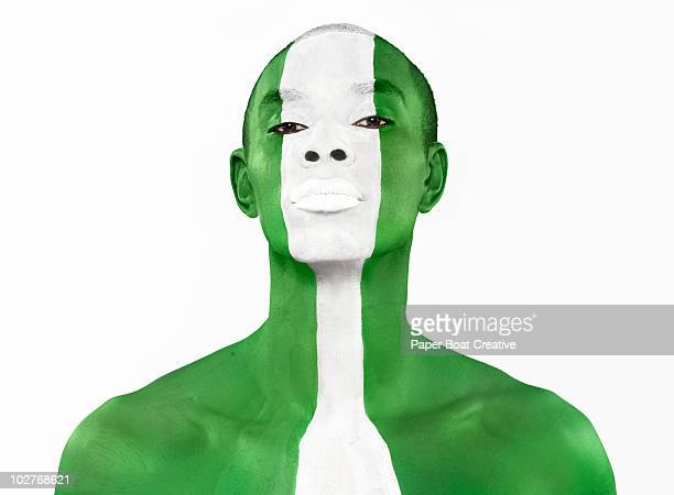 nigerian flag painted on man's face - nigerian flag stock photos and pictures