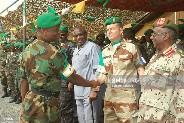 Nigerian Force Commander Major General Festus Okonkwo of the African Union mission in Sudan shakes hands with unidentified millitary officials as...