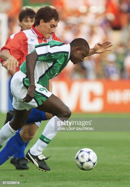Nigerian forward Rasheed Yekini runs past an unidentified Paraguyan player 24 June at the Stadium in Toulouse south of France during the 1998 Soccer...