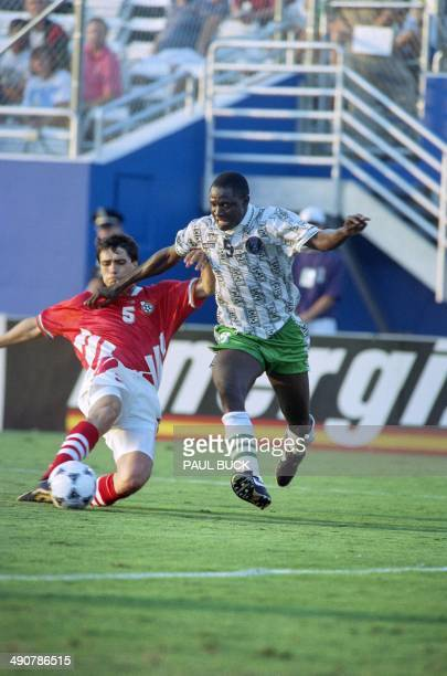 Nigerian forward Rashidi Yekini attempts to steal the ball from Bulgarian defender Peter Houbtchev during the World Cup match on June 21 1994 at the...