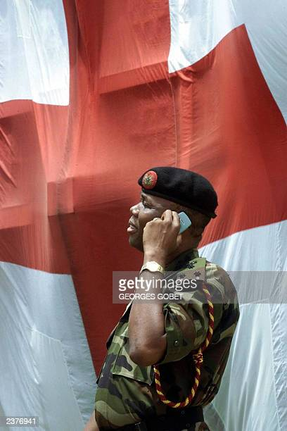 Nigerian General Festus Okonkwo leader of the ECOWAS advance military delegation speaks on the phone in Monrovia 31 July 2003 during a tour of the F...
