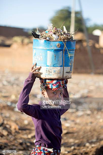 Nigerian girl collecting junk and garbage in a bucket at a garbage dump on December 07 in Niamey Niger Photo by Ute Grabowsky/Photothek via Getty...