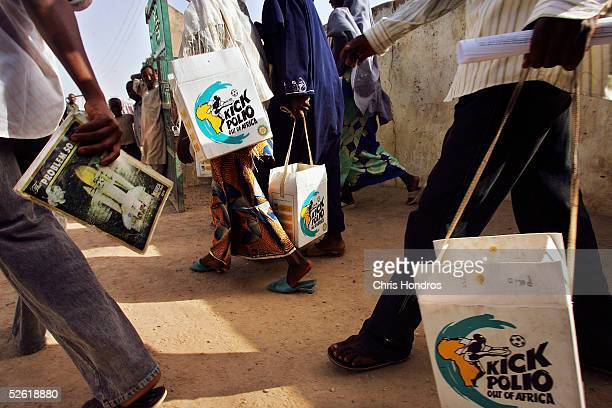 Nigerian health workers set out with their insulated boxes of vaccine during a nationwide polio innoculation on April 12 in Kano Nigeria...