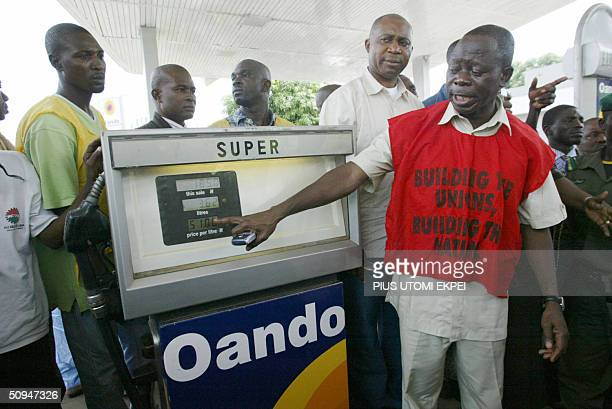 Nigerian Labour Congress President Adams Oshiomhole points to the old fuel price at an Abuja filling station calling for immediate correction in...