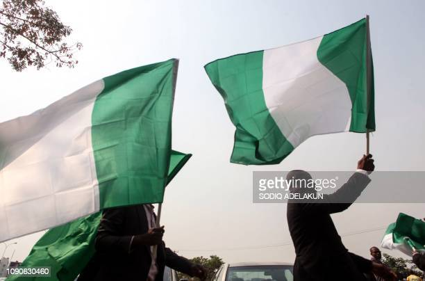 Nigerian lawyers hold up the national flag as they assemble at the secretariat of the Nigerian Bar Association during a protest in Abuja over the...