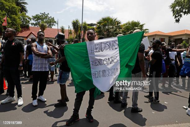 Nigerian man based in South Africa holds a Nigerian national flag while protesting outside their embassy in Pretoria on October 21, 2020 in...