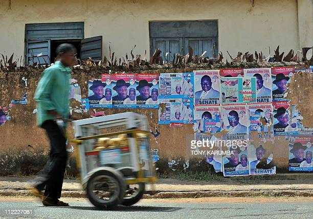 A Nigerian man hawks snacks along a street lined with destroyed postrers advertising Presidential candidate Jonathan Goodluck at Jos the...