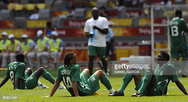 Nigerian midfielder Sani Kaita forward Peter Odemwingie and defender Dele Adeleye look dejected after Argentina won the men's Olympic football final...