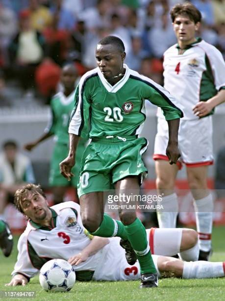Nigerian midfielder Victor Ikpeba scores a goal as Bulgarian defender and captain Trifon Ivanov lies on the ground and teammate Ivaylo Petkov looks...