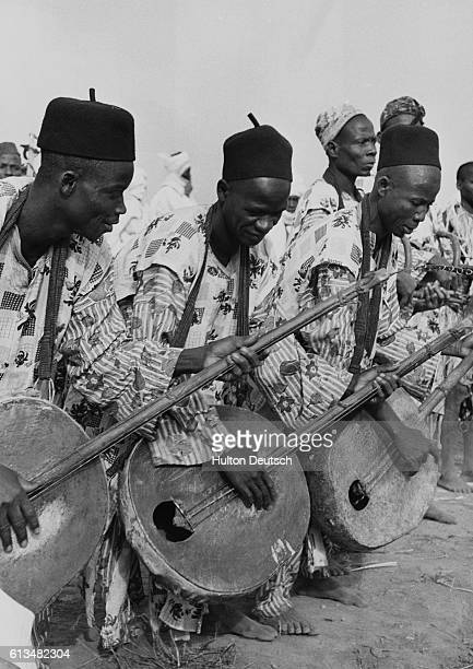 Nigerian musicians greet the Queen during her 1956 tour as they play their stringed instruments for her arrival in Kaduna | Location Durbar Kaduna...