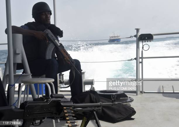 A Nigerian naval member sits in a vessel during Obangame Express a multinational maritime exercise involving 33 countries off the coast of Lagos on...