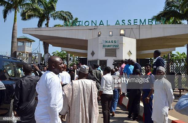 Nigerian parliament members gather at the national assembly gate closed by security forces in Abuja on November 20 2014 Nigerian police fired teargas...