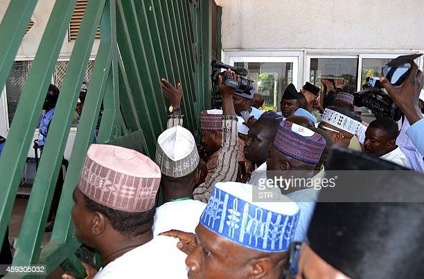 Nigerian parliament members gather in front of the national assembly gate closed by security forces in Abuja on November 20 2014 Nigerian police...