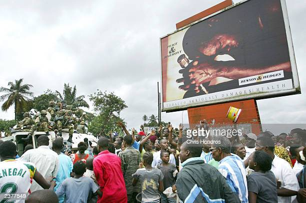 Nigerian peacekeepers wade through cheering crowds of Liberians as they make their first rounds through the center of Monrovia August 7 2003 in...