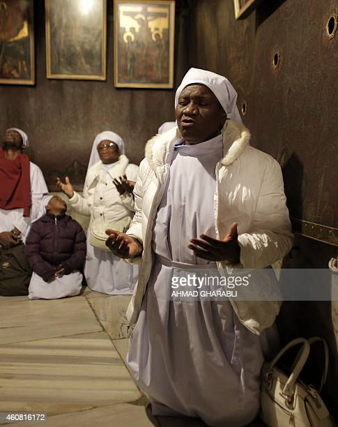 Nigerian pilgrims pray as part of Christmas celebrations inside the Grotto at the Church of the Nativity believed to be the birthplace of Jesus...