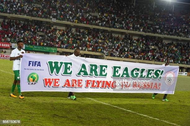 Nigerian players carry a banner to celebrate qualifying after the FIFA World Cup 2018 qualifying football match between Nigeria and Zambia in Uyo...