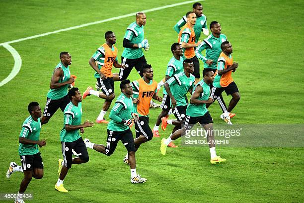 Nigerian players run during a training session at the Baixada Arena in Curitiba on June 15 on the eve of their Group F 2014 FIFA World Cup football...