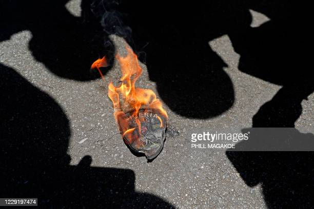 Nigerian police emblem is seen burning based during a protest outside their embassy in Pretoria on October 21, 2020 in solidarity with Nigerian youth...