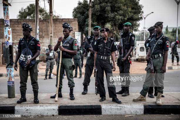 Nigerian police monitor an area where All Progressives Congress Party supporters are celebrating after initial results were released by the Nigerian...