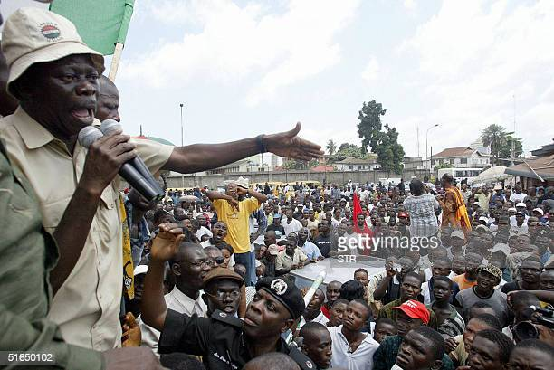 Nigerian police officer Dan Adegbuyi tries to stop President of the Nigerian Labour Congress Adams Oshiomhole from addressing a crowd 03 November...