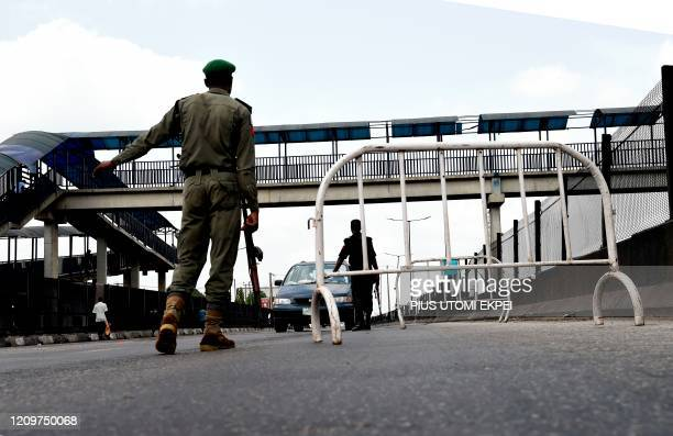 Nigerian police officer flags down an on coming vehicle at a checkpoint to enforce the extended lockdown as part of measures to prevent the spread of...