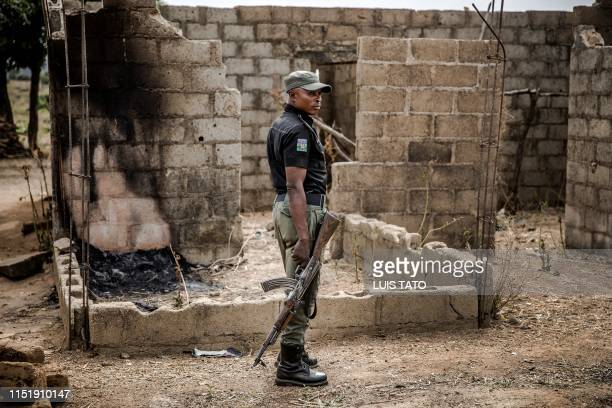 A Nigerian Police Officer patrols an area of destroyed and burned houses after a recent Fulani attack in the Adara farmers' village of Angwan Aku...