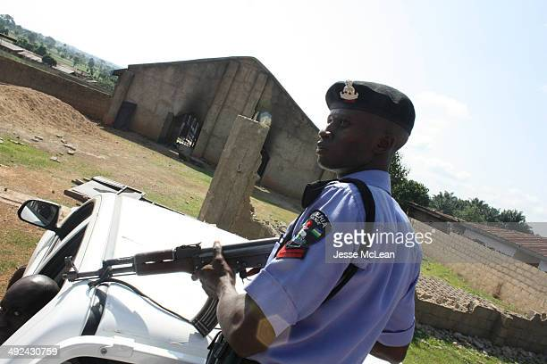 Nigerian police officer watches over the charred Nasara Baptist Church in Kachia destroyed by a fire during three days of religious clashes between...
