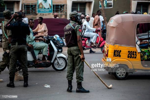 A Nigerian police officer wearing a gas mask and holding a stick monitors an area where All Progressives Congress Party supporters are celebrating...
