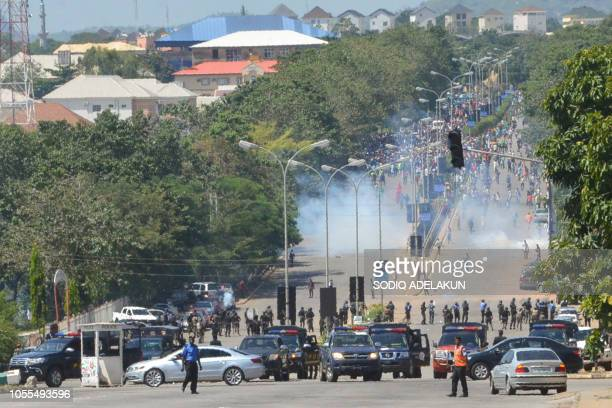 Nigerian police officers fire teargas at supporters of Islamic Movement of Nigeria as they protest against the imprisonment of their leader Ibrahim...