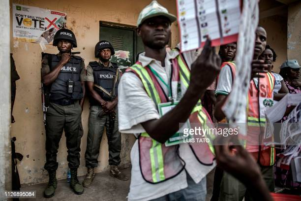 Nigerian Police Officers monitor the counting of votes at Shagari Primary School polling station in Yola Adamawa State on February 23 2019 after the...