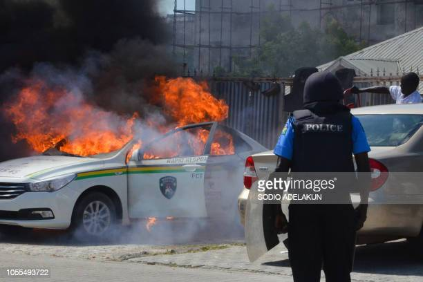 A Nigerian police officers watches a police vehicle as it goes up in flames following clashes with supporters of Islamic Movement of Nigeria...