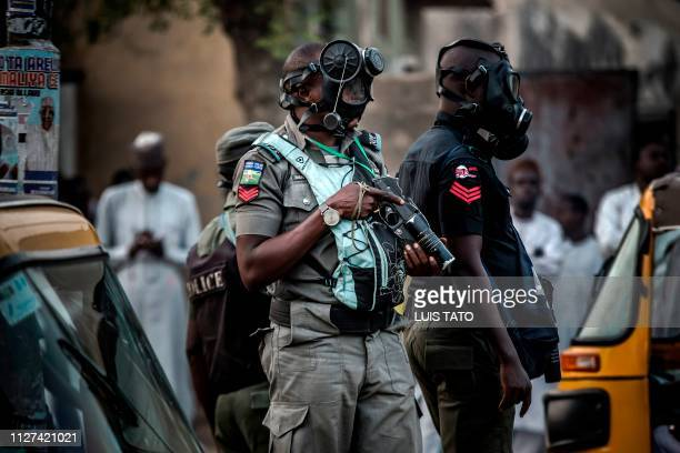Nigerian police wearing gas masks monitor an area where All Progressives Congress Party supporters celebrate initial results released by the Nigerian...