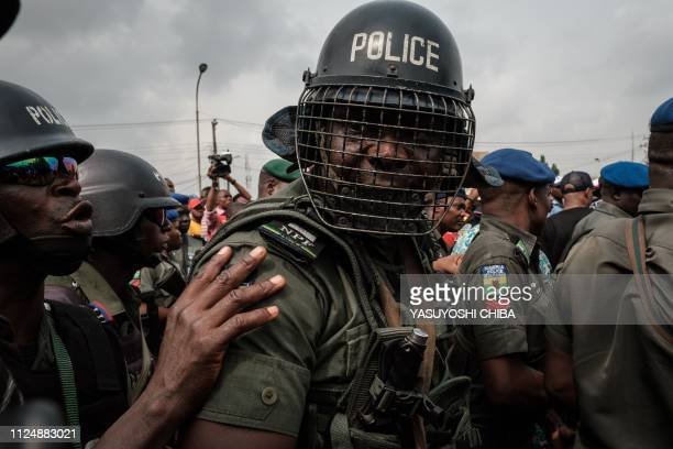 TOPSHOT Nigerian police's antiriot unit secure the main gate of the local office during the protest by supporters of the All Progressives Congress in...