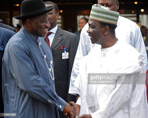 Nigerian President and Economic Community of West African States chairman Goodluck Jonathan shakes hands with founding father of ECOWAS General...