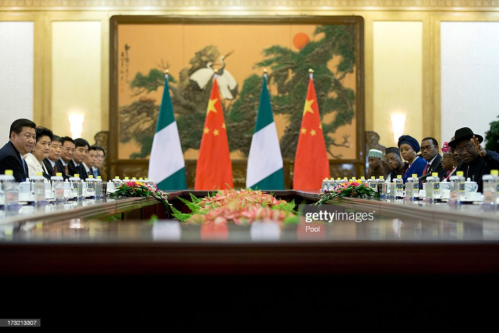 Nigerian President Goodluck Jonathan, (R) gestures to introduce ministers of his cabinet while Chinese President Xi Jinping, (L) watches during their meeting at the Great Hall of the People in Beijing, China, Wednesday, July 10, 2013. The Nigerian president was in China to finalise low interest loans to help with Nigeria's infrastructure.
