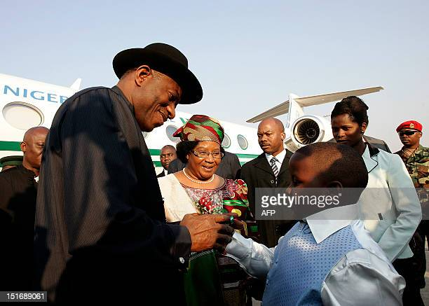 Nigerian President Goodluck Jonathan receives a gift as he is welcomed by Malawi's President Joyce Banda at Kamuzu International Airport in Lilongwe...
