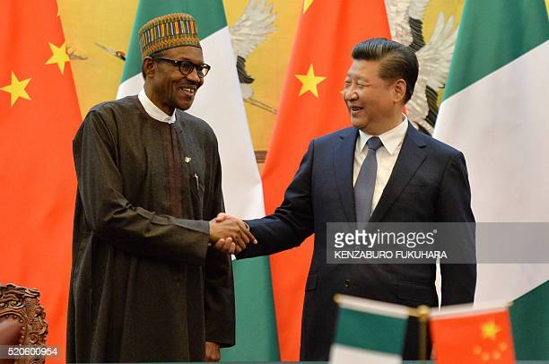 Nigerian President Muhammadu Buhari and Chinese President Xi Jinping shake hands during a signing ceremony at the Great Hall of the People in Beijing...