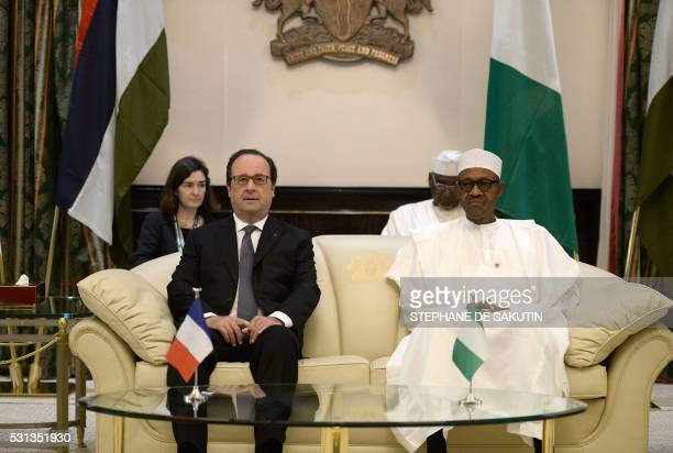 Nigerian President Muhammadu Buhari and French President Francois Hollande look on during a meeting at the presidential Palace in Abuja on May 14...