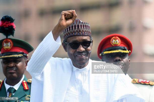 Nigerian President Muhammadu Buhari raises his fist during an inspection of honour guards on parade to mark Democracy Day in Abuja on June 12 2019...