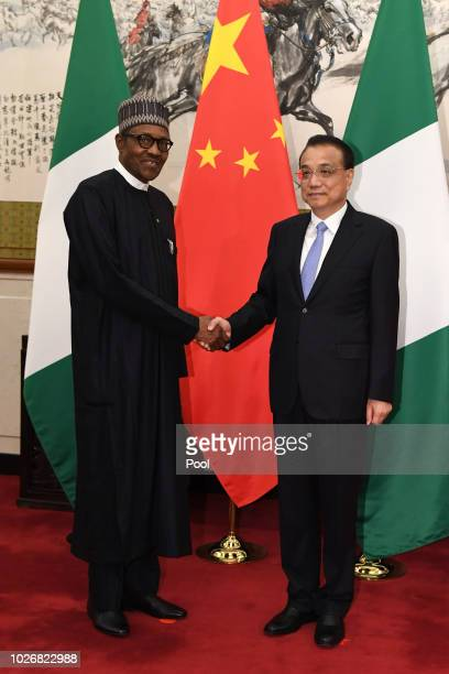 Nigerian President Muhammadu Buhari shakes hands with Chinese Premier Li Keqiang before their meeting at the Diaoyutai State Guesthouse in Beijing...