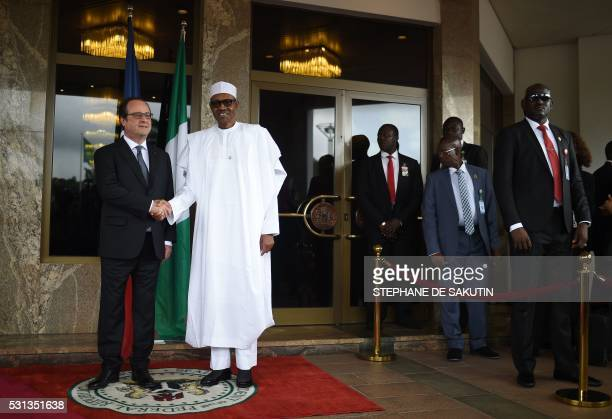 Nigerian President Muhammadu Buhari shakes hands with French President Francois Hollande as he welcomes him prior to a meeting at the presidential...