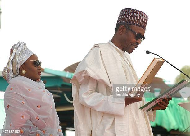 Nigerian President Muhammadu Buhari takes his oath of office with his wife Aisha Buhari the new first lady of Nigeria during his inauguration...
