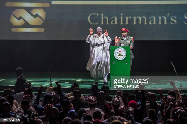 TOPSHOT Nigerian president Muhammadu Buhari waves at the crowd in Lagos on March 29 as he attends the rally organized to celebrate the 66th birthday...